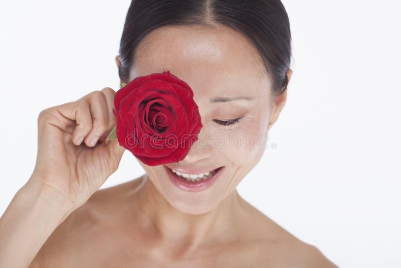 Ono uśmiecha się, piękna, bez koszuli kobieta trzyma czerwieni róży jej oko, studio strzał zdjęcia stock