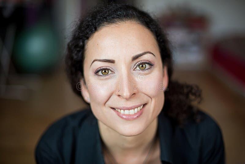 Ono uśmiecha się, rozochocona i życzliwa kobieta z zielonymi oczami z kolorowym tłem, zdjęcie royalty free