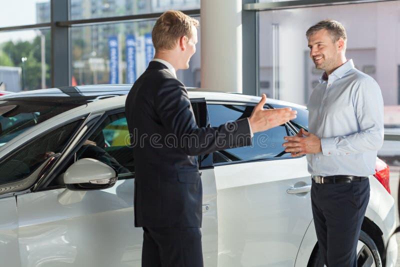 Ono uśmiecha się samochodowy handlowiec zdjęcia royalty free