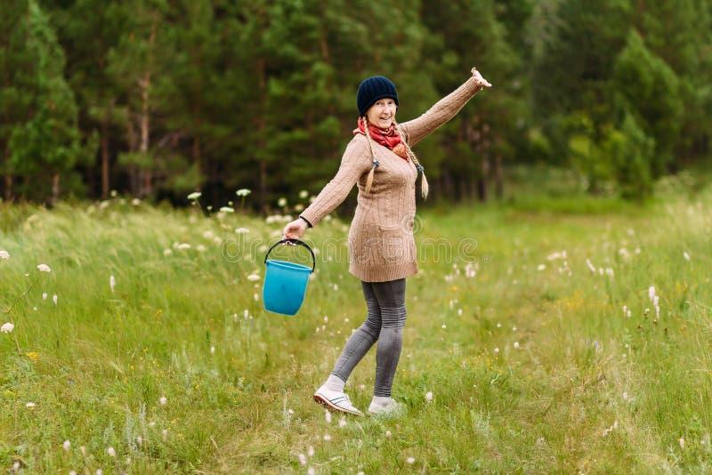 Ono uśmiecha się, szczęśliwa przechodzić na emeryturę kobieta iść przez drewien z wiadrem fotografia stock