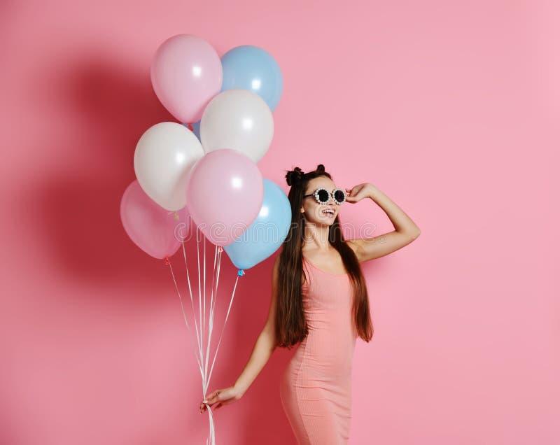 , ono uśmiecha się szeroko i bawić się z baloons błękita i menchii w górę ślicznej blond dziewczyny pozycji w studiu zdjęcie stock