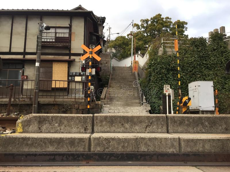 Old train intersection with old building, Onomichi, Hiroshima, Japan. Onomichi, Hiroshima, Japan - 18th December, 2017: Old train intersection with old building stock photo