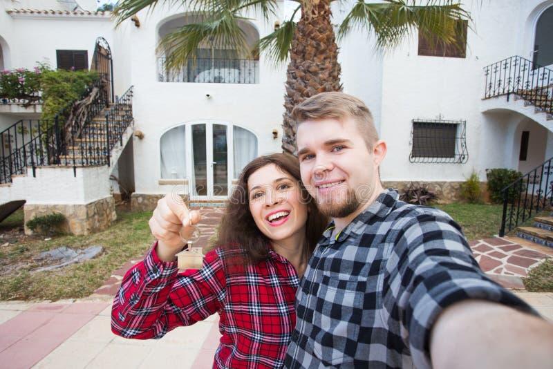 Onroerende goederen bezit, en flatconcept - het Gelukkige grappige jonge paar tonen sleutels van hun nieuw huis stock afbeelding