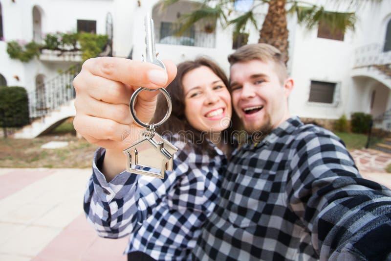 Onroerende goederen bezit, en huurconcept - het Gelukkige het glimlachen jonge paar tonen sleutels van hun nieuw huis royalty-vrije stock afbeelding