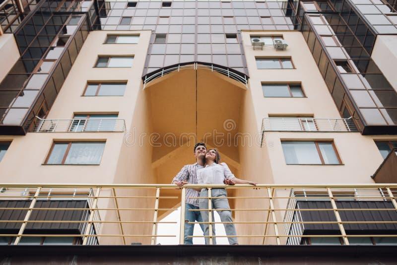 Onroerende goederen en familieconcept Jong paar op voorzijde van nieuw groot modern huis hun nieuw huis royalty-vrije stock foto's