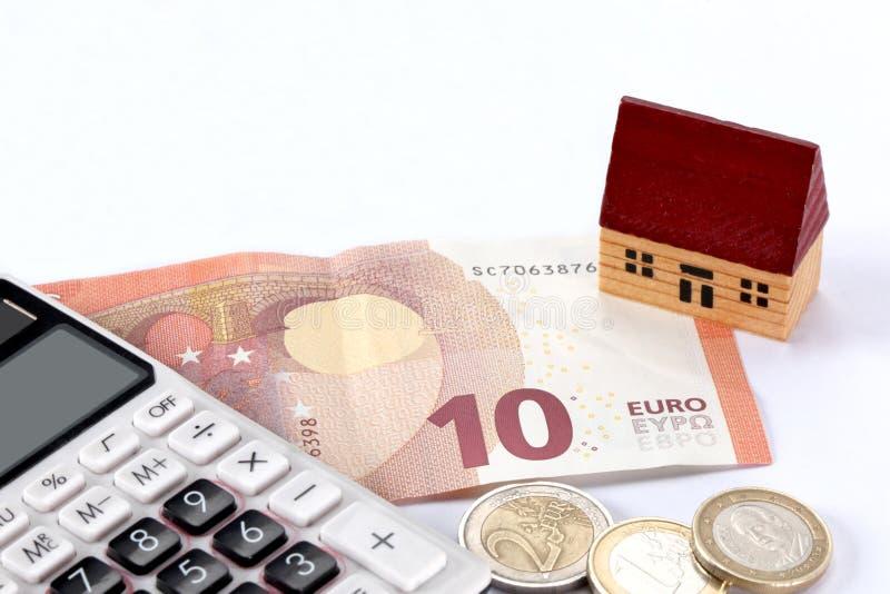 Onroerende goederen en hypotheekconcept: stuk speelgoed huis, euro rekening, muntstukken en een calculator op witte achtergrond m royalty-vrije stock foto