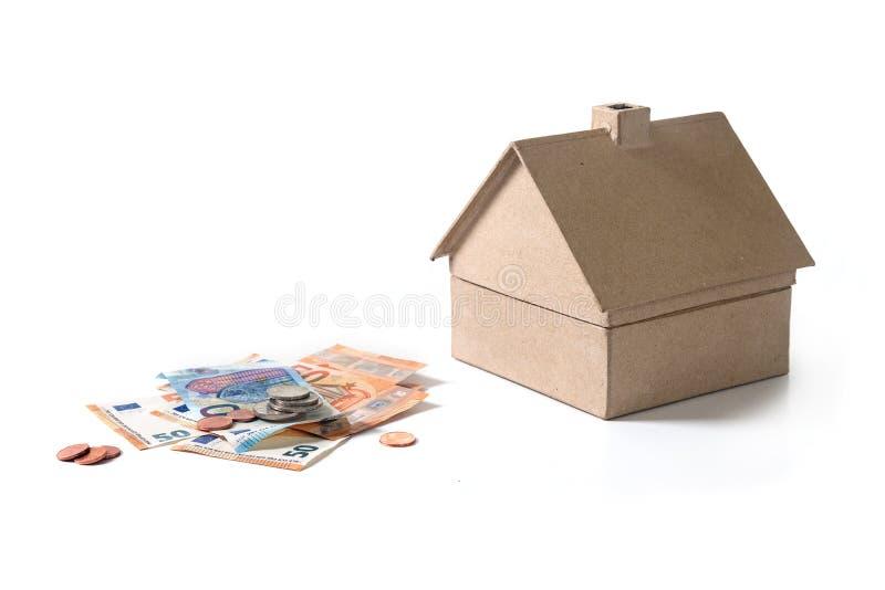 Onroerende goederen huis van karton naast euro bankbiljetten en muntstukken, stock fotografie