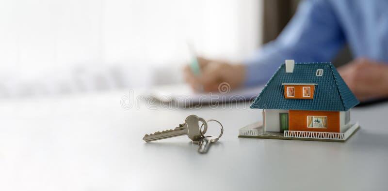 Onroerende goederenbedrijfsconcept - het model en de sleutels van de nieuw huisschaal op de lijst op makelaar in onroerend goedka royalty-vrije stock afbeeldingen