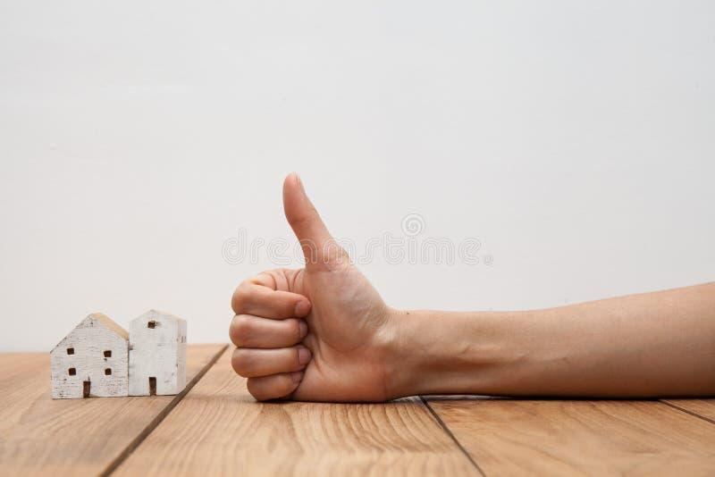 Onroerende goederenconcept een hand die duim tonen bij miniatuurhuis royalty-vrije stock fotografie