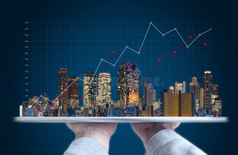 Onroerende goederenhandelsinvesteringen en bouwtechnologie Hand die digitale tablet met gebouwenhologram houden en grafiek opheff royalty-vrije stock afbeelding