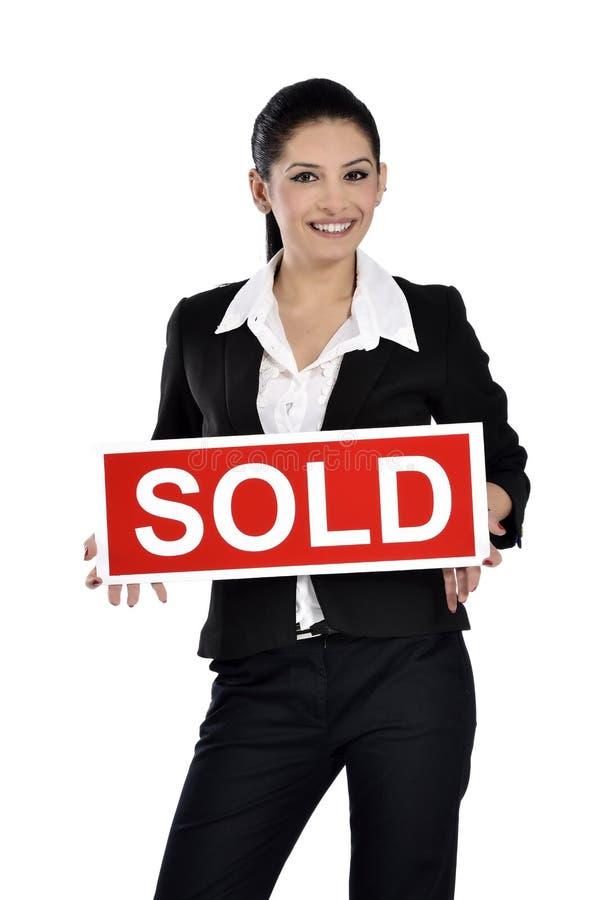 Onroerende goederenvrouw die een verkocht teken houden stock foto
