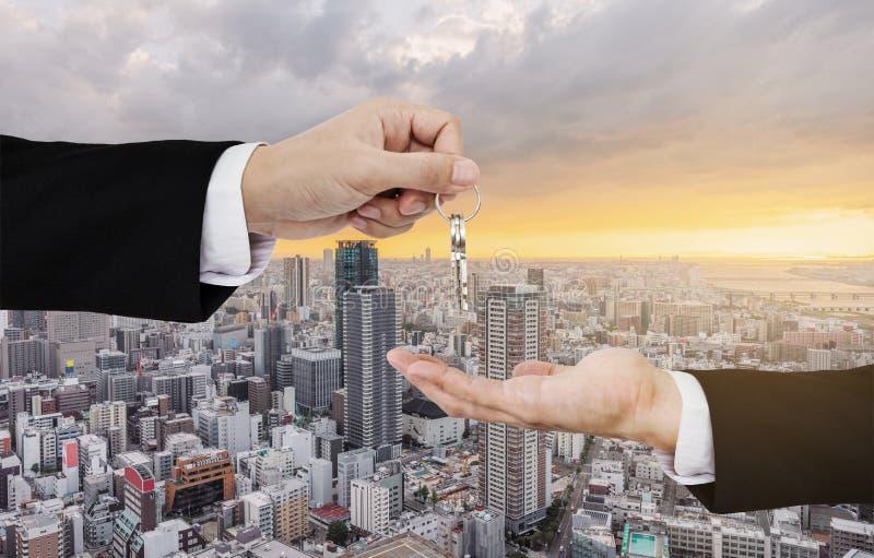Onroerende goederenzaken, woonhuur en investering De sleutels van de zakenmanoverdracht, met de achtergrond van de stadszonsopgan royalty-vrije stock afbeeldingen