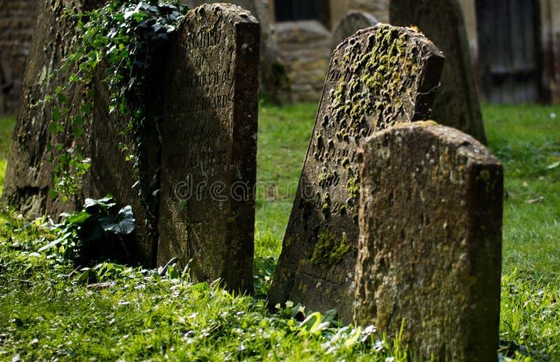Onschadelijk gemaakt beeld van Grafstenen in een kerkhof stock afbeeldingen