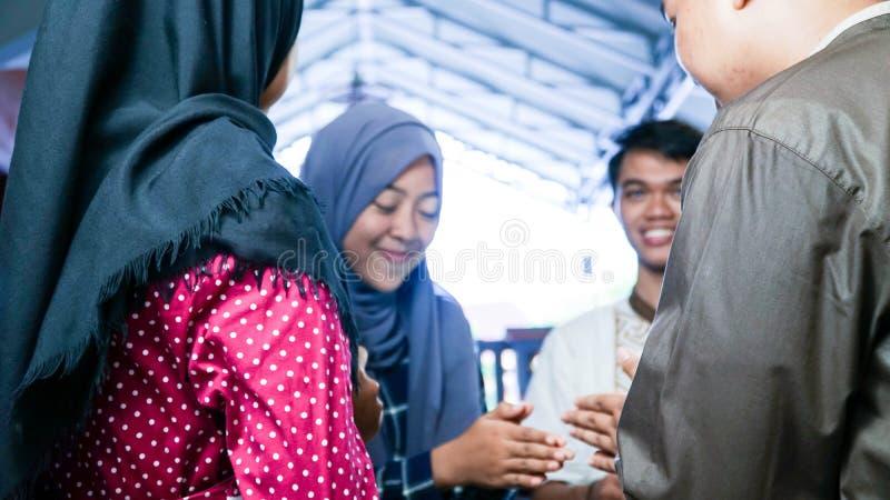 Onscherp portret van Moslimparen die hun familie of vriendenhuis bezoeken terwijl het schudden en omhelzingen op de viering van e royalty-vrije stock foto's