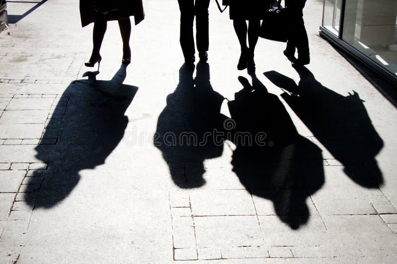 Onscherp schaduwsilhouet van mensen die in hoog contrast lopen stock fotografie