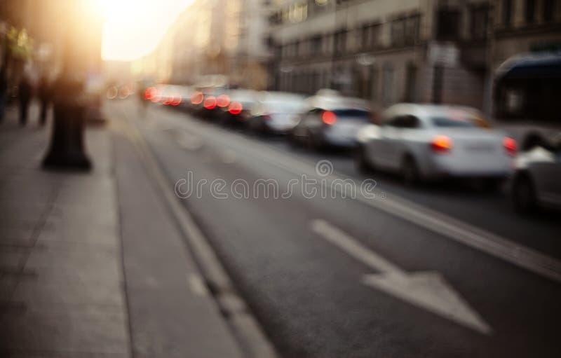 Onscherp unfocused achtergrond met de stedelijke weg met vervoer in zonsondergangverlichting royalty-vrije stock afbeeldingen