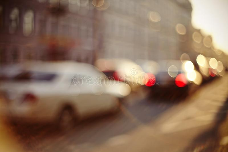 Onscherp unfocused achtergrond met de stedelijke weg met vervoer in zonsondergangverlichting royalty-vrije stock fotografie