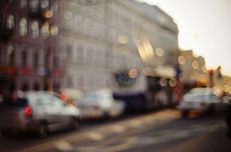 Onscherp unfocused achtergrond met de stedelijke weg met vervoer in zonsondergangverlichting stock foto's