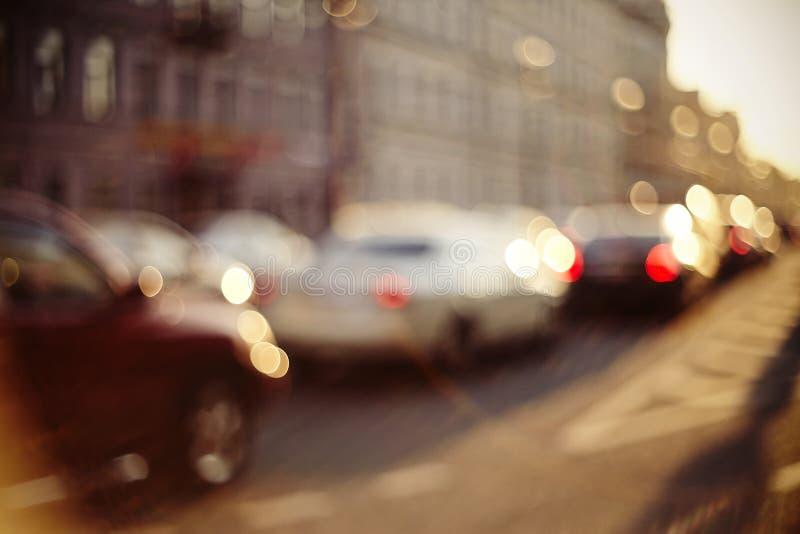 Onscherp unfocused achtergrond met de stedelijke weg met vervoer in zonsondergangverlichting stock foto