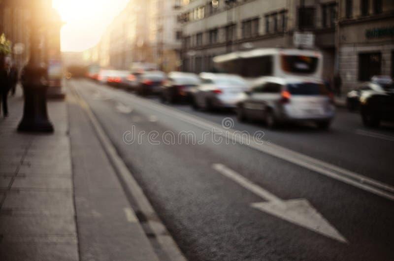 Onscherp unfocused achtergrond met de stedelijke weg met vervoer in zonsondergangverlichting stock fotografie