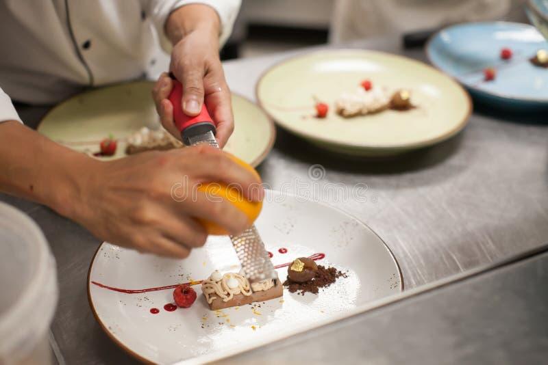 Onscherpe achtergrond, Dessert met de sinaasappelschil van de chef-kokdia op bovenkant stock foto's