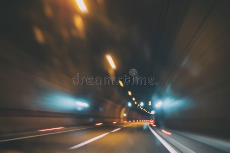 Onscherpe autotunnel met lichten, de achtergrond van het motieonduidelijke beeld royalty-vrije stock fotografie