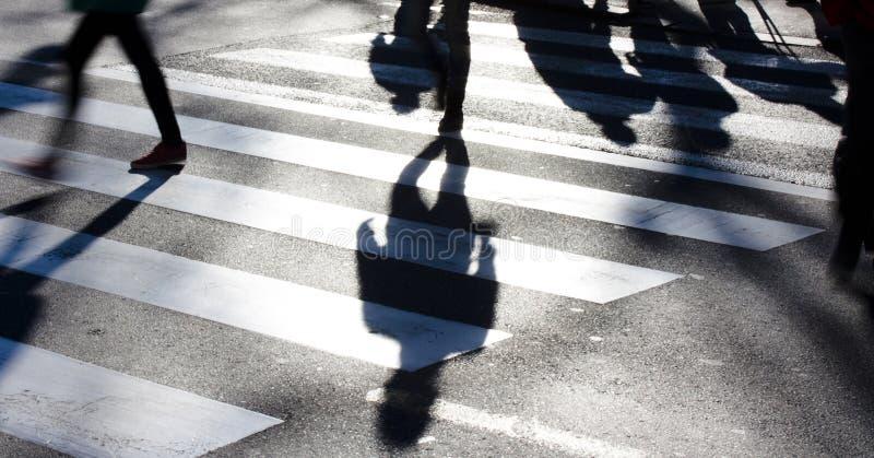 Onscherpe gestreepte kruising met voetgangers die lange schaduwen maken royalty-vrije stock afbeelding