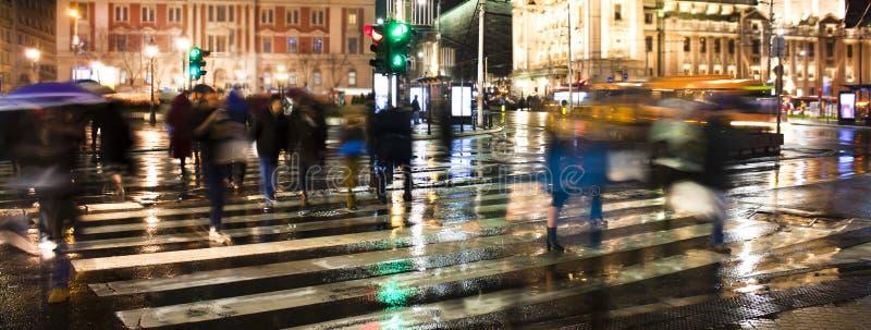 Onscherpe mensen die de stadsstraat in regenachtige nacht kruisen royalty-vrije stock afbeelding