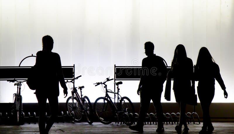 Onscherpe silhouetten van jongeren die in de zwart-witte nacht lopen stock afbeelding