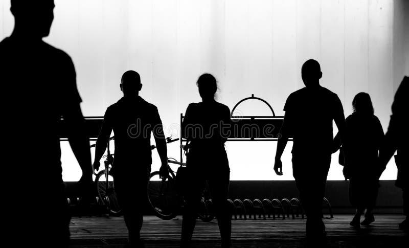 Onscherpe silhouetten van jongeren die in de zwart-witte nacht lopen stock foto's