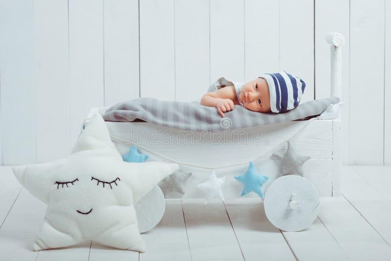 onschuldige weinig zuigelingsbaby die in houten liggen stock afbeelding