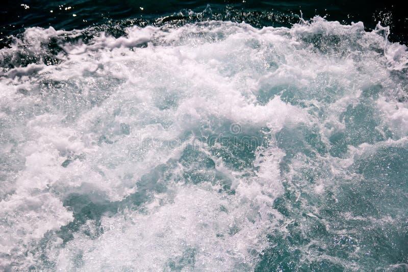 Onstuimigheid door schuim van zeewater van een hoge snelheidsjacht wordt gemaakt op oppervlakte van overzees die Blauwe overzeese stock foto