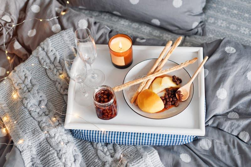 Ontbijt in bed, een dienblad met kaas, grissini, jam van jonge sparappel, champagne en een kaars De ochtend van Kerstmis honeymoo royalty-vrije stock afbeeldingen
