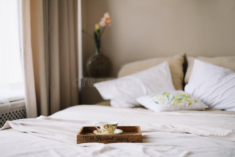 Ontbijt in bed Houten dienblad met koffiekop Bed met sprei, witte bladen en hoofdkussens en een kop Witte slaapkamer Vlak leg stock fotografie