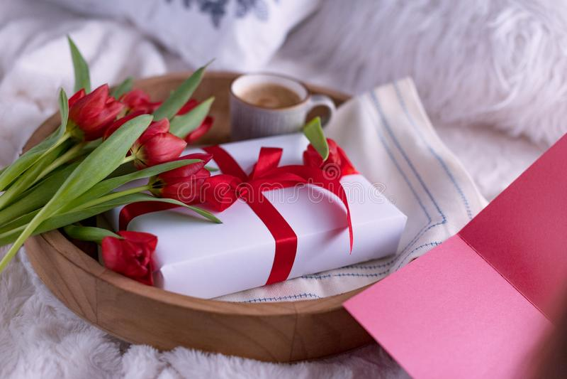 Ontbijt in bed op een dienblad met bloemen en een doos met een boog als gift Het concept de vakantie van de dag en Maart van de m stock afbeeldingen