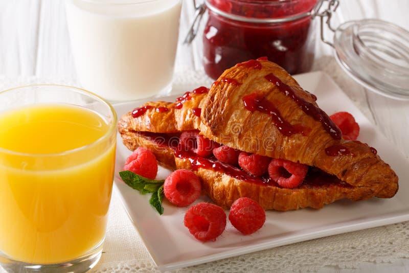 Ontbijt: croissant met frambozen en jam, jus d'orange en royalty-vrije stock afbeeldingen