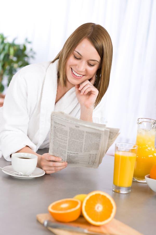 Ontbijt - de krant van de vrouwenlezing in keuken stock afbeeldingen