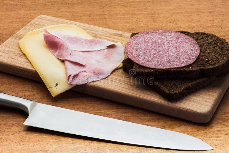 Ontbijt of de lunch die met hamkaas een bruine sandwich het plaatsen paneert op houten raad stock foto