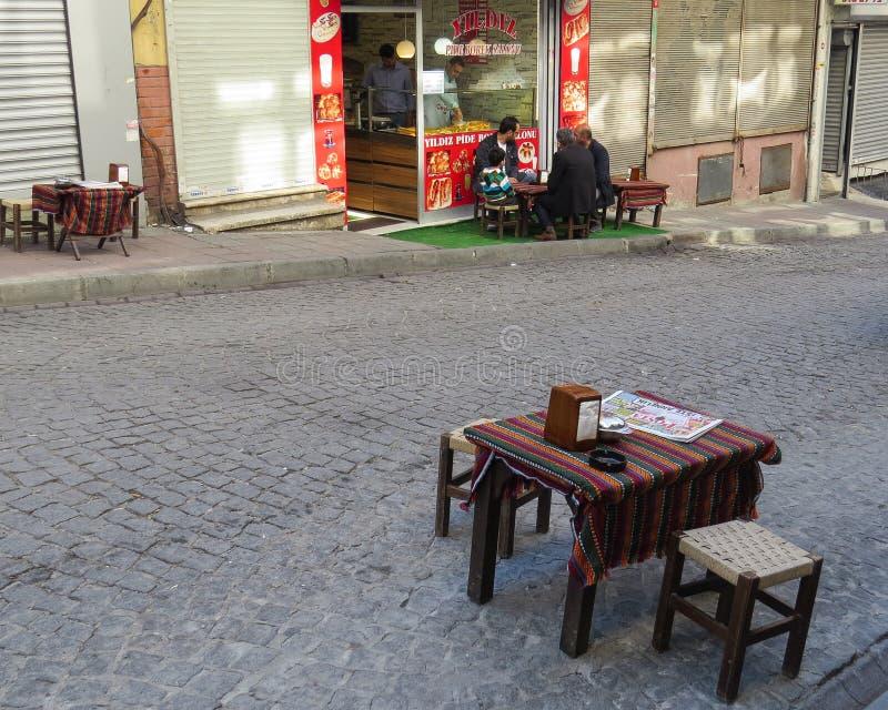 Ontbijt in de straatkoffie met het lezen van het nieuws in de krant Het ritueel van de ochtendstad stock fotografie