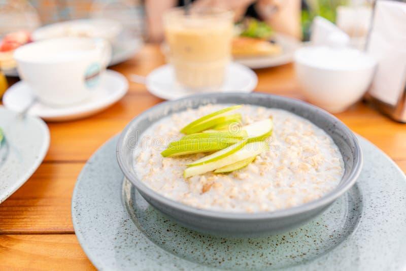 Ontbijt en koffie in de de zomerkoffie Verse havermeelhavermoutpap met appelen, honing, noten en kaneel dichte omhooggaand voor royalty-vrije stock fotografie