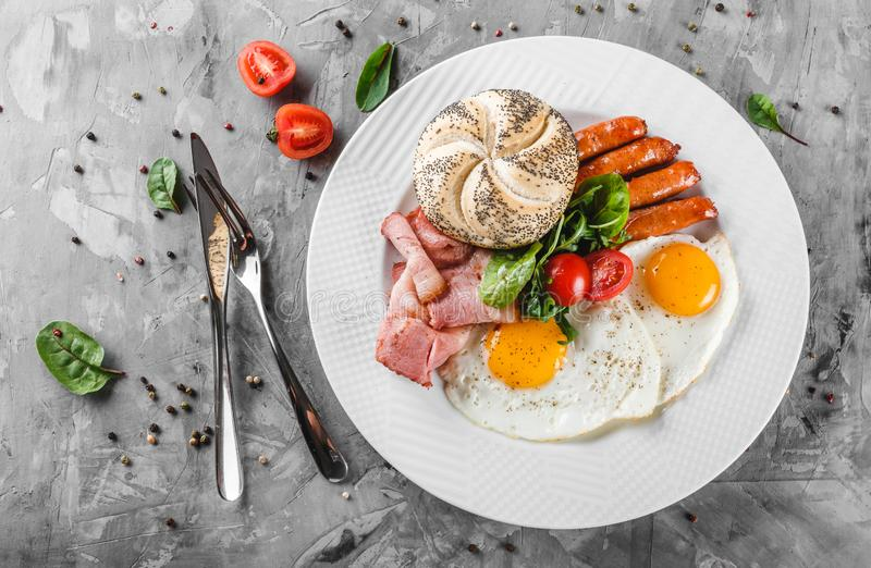 Ontbijt, gebraden eieren, broodje, worst, bacon, prosciutto, verse salade op plaat op grijze lijstoppervlakte Gezond voedsel, hoo royalty-vrije stock foto's