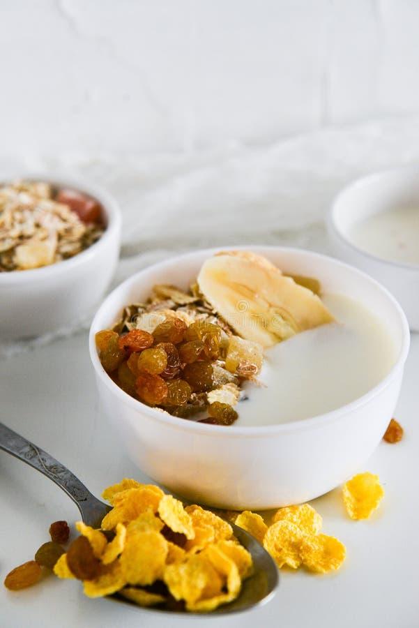 Ontbijt in glaskop: eigengemaakte granola, banaan, verse bessen, yoghurt op witte achtergrond Het concept het gezonde eten, hoog- stock foto's