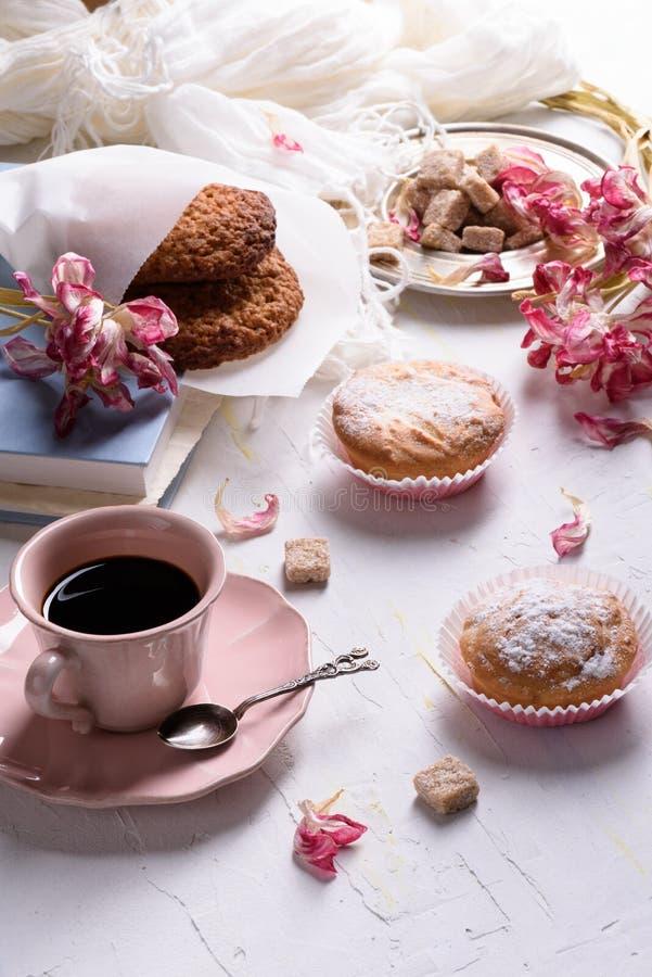 Ontbijt - haverkoekjes, vanillemuffins met suikersuikerglazuur, zwarte koffie Close-up, witte lijst, ochtendlicht stock afbeeldingen