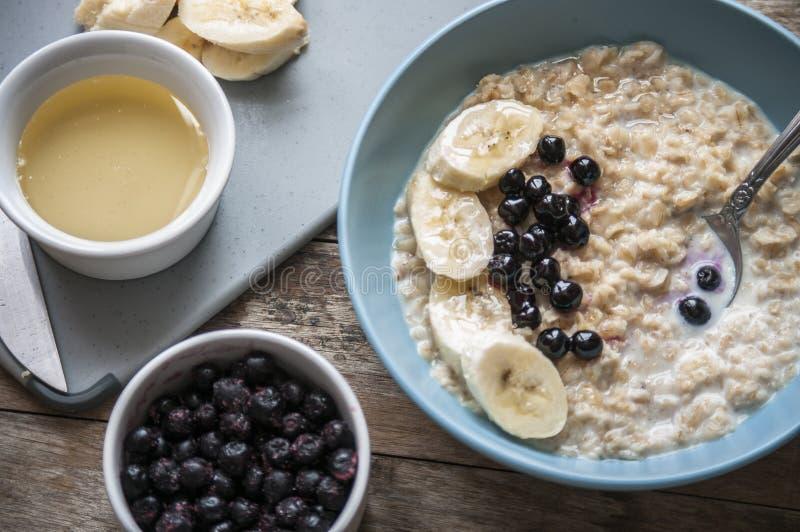 Ontbijt: havermeel met bananen en bosbessen stock fotografie