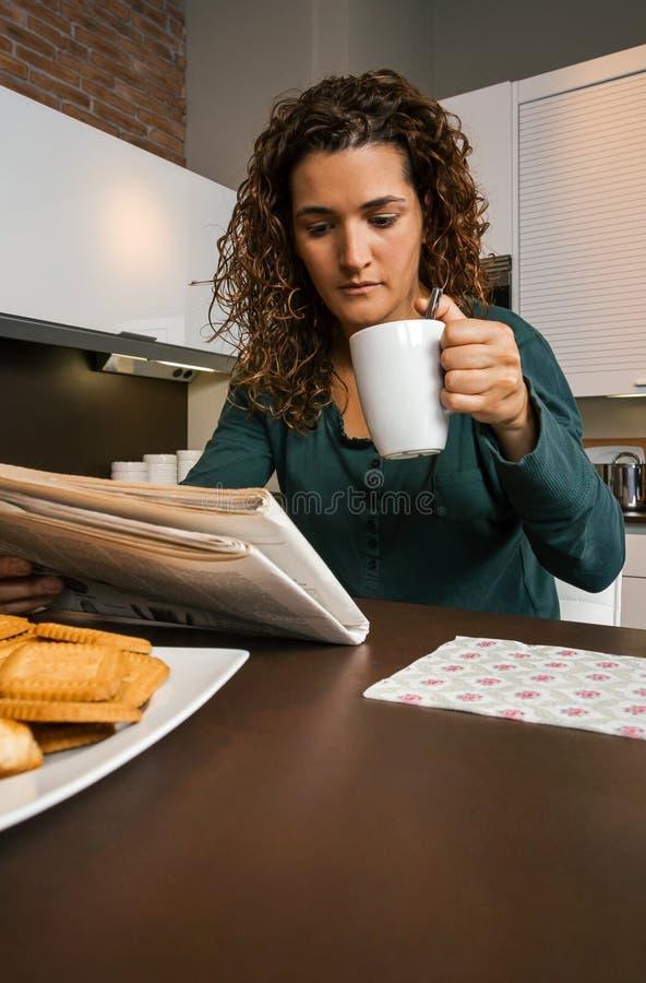 Ontbijt hebben en vrouw die krant kijken royalty-vrije stock afbeelding