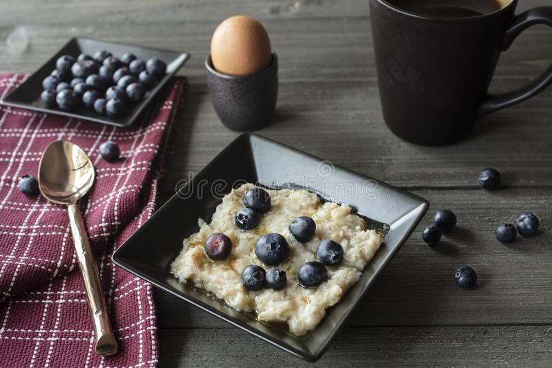Ontbijt het Dienen van Havermeel met Bluberries, Koffie en Ei op een Uitstekende Lijst royalty-vrije stock afbeelding