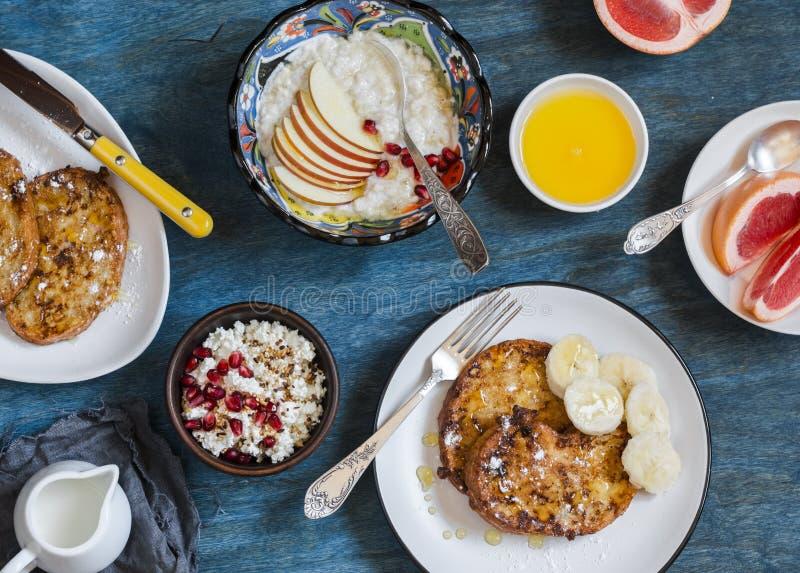 Ontbijt - karamel Franse toost met banaan, kwark met granola en granaatappel, havermeelhavermoutpap, verse grapefruit op a stock fotografie