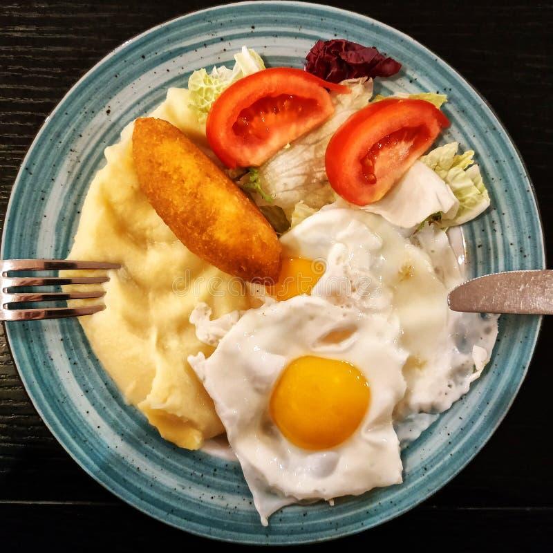 Ontbijt met aardappels, ei, kotelet en salade stock afbeelding