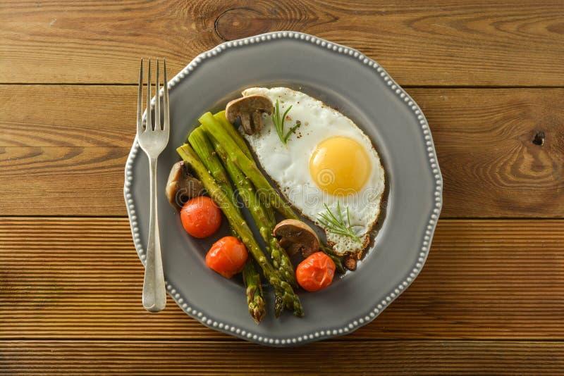 Ontbijt met asperge, gebraden ei en kersentomaten Houten lijst stock fotografie