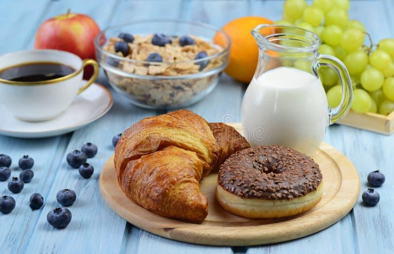 Ontbijt met croissant, doughnut, koffie, graangewas en vruchten stock foto